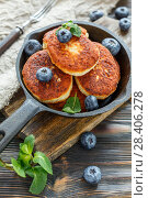 Купить «Cheese pancakes and blueberries in cast iron pan», фото № 28406278, снято 20 февраля 2018 г. (c) Марина Сапрунова / Фотобанк Лори