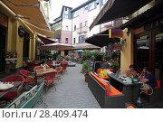Купить «Уличные кафе на узкой улице Тбилиси. Грузия», эксклюзивное фото № 28409474, снято 13 июля 2017 г. (c) Алексей Гусев / Фотобанк Лори