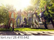 Купить «happy teenage students or friends jumping outdoors», фото № 28410642, снято 21 мая 2016 г. (c) Syda Productions / Фотобанк Лори