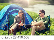 Купить «happy couple drinking beer at campsite tent», фото № 28410666, снято 27 мая 2016 г. (c) Syda Productions / Фотобанк Лори