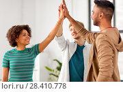 Купить «happy creative team making high five at office», фото № 28410778, снято 11 марта 2018 г. (c) Syda Productions / Фотобанк Лори