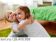 Купить «happy little girls or sisters hugging at home», фото № 28410950, снято 15 октября 2017 г. (c) Syda Productions / Фотобанк Лори
