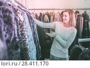 Купить «Cheerful woman customer examining best fur coats», фото № 28411170, снято 24 января 2020 г. (c) Яков Филимонов / Фотобанк Лори