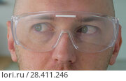 Купить «close up of male face in safety glasses or goggles», видеоролик № 28411246, снято 12 мая 2018 г. (c) Syda Productions / Фотобанк Лори