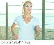 Smiling adult woman in white T-shirt is jogging on the beach. Стоковое фото, фотограф Яков Филимонов / Фотобанк Лори