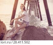Купить «Elegant woman is resting on the rocks in her free time», фото № 28411502, снято 17 июля 2017 г. (c) Яков Филимонов / Фотобанк Лори