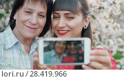 Купить «Mother and daughter make a photo», видеоролик № 28419966, снято 2 мая 2018 г. (c) Илья Шаматура / Фотобанк Лори