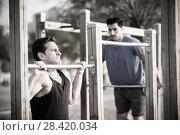 Купить «Two friends 30 years old are doing pull-ups for strength», фото № 28420034, снято 6 сентября 2017 г. (c) Яков Филимонов / Фотобанк Лори