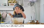 Купить «Little girl baker taste the cookie dough», видеоролик № 28421274, снято 27 мая 2020 г. (c) Константин Шишкин / Фотобанк Лори