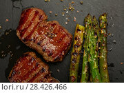 Close up grilled beef steaks on black slate board. Стоковое фото, фотограф Anton Eine / Фотобанк Лори