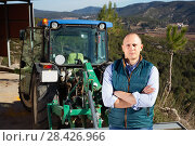 Купить «Confident male owner of vineyard posing near tractor outdoors in sunny day», фото № 28426966, снято 22 января 2018 г. (c) Яков Филимонов / Фотобанк Лори
