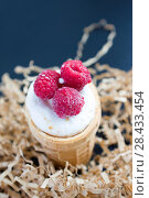 Ice cream with raspberry in waffle cone on wood. Стоковое фото, фотограф Papoyan Irina / Фотобанк Лори