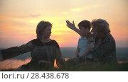 Купить «Grandmother, mother with little son on the hill swatting at mosquitoes at sunset», видеоролик № 28438678, снято 18 июня 2019 г. (c) Константин Шишкин / Фотобанк Лори