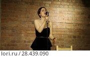 Купить «Красивая молодая певица с винтажным микрофоном на фоне кирпичной стены», видеоролик № 28439090, снято 23 октября 2018 г. (c) Евгений Ткачёв / Фотобанк Лори