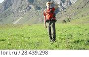 Купить «Hiking man walking on green mountain meadow with backpack. Summer sport and recreation concept.», видеоролик № 28439298, снято 18 апреля 2018 г. (c) Александр Маркин / Фотобанк Лори