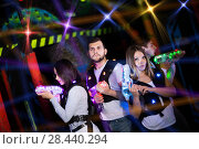 Купить «Young people playing laser tag in bright beams», фото № 28440294, снято 25 апреля 2018 г. (c) Яков Филимонов / Фотобанк Лори