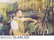 Купить «Young guy choosing flak jacket in military shop», фото № 28440426, снято 4 июля 2017 г. (c) Яков Филимонов / Фотобанк Лори
