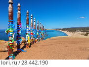 Купить «Lake Baikal. A sacred place near Khuzhir village. Tourists tie colored ribbons on poles and make wishes. On earth coins of different countries from travelers who want to return again», фото № 28442190, снято 19 мая 2018 г. (c) Виктория Катьянова / Фотобанк Лори