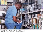 Купить «African American salesman checking goods availability on shelves of building materials shop», фото № 28442462, снято 12 апреля 2018 г. (c) Яков Филимонов / Фотобанк Лори