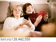 Купить «Two senior women with phones on sofa», фото № 28442550, снято 22 ноября 2017 г. (c) Яков Филимонов / Фотобанк Лори