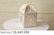 Купить «White vintage paper box for gifts turns on a stand against a white wooden wall. 4k video», видеоролик № 28449998, снято 21 мая 2018 г. (c) Happy Letters / Фотобанк Лори