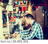 Купить «Male worker stitching new belt», фото № 28450302, снято 23 июля 2018 г. (c) Яков Филимонов / Фотобанк Лори