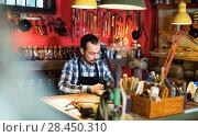 Купить «Male worker working on leather for belt in leather», фото № 28450310, снято 23 июля 2018 г. (c) Яков Филимонов / Фотобанк Лори