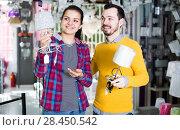 Купить «Couple looking at lamp options», фото № 28450542, снято 16 февраля 2017 г. (c) Яков Филимонов / Фотобанк Лори