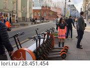 Купить «Девушка у пункта проката электросамокатов на Большой Дмитровке в Москве», фото № 28451454, снято 22 мая 2018 г. (c) Дмитрий Рыженков / Фотобанк Лори