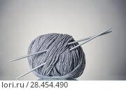 Купить «Coil of gray yarn and needles for needlework, on gray», фото № 28454490, снято 12 января 2018 г. (c) Сергей Молодиков / Фотобанк Лори