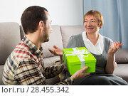 Купить «Son gives gift to mother», фото № 28455342, снято 19 марта 2019 г. (c) Яков Филимонов / Фотобанк Лори