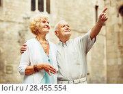 Купить «Senior man pointing to his wife at some landmark during walk around city», фото № 28455554, снято 24 мая 2018 г. (c) Яков Филимонов / Фотобанк Лори