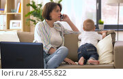Купить «working mother with baby calling on smartphone», видеоролик № 28455822, снято 19 мая 2018 г. (c) Syda Productions / Фотобанк Лори