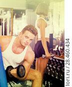 Купить «friendly young man making biceps curls in gym», фото № 28460434, снято 4 октября 2016 г. (c) Яков Филимонов / Фотобанк Лори