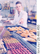 Купить «Young man choosing what kind of meat to buy», фото № 28460450, снято 20 октября 2016 г. (c) Яков Филимонов / Фотобанк Лори