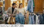Купить «Couple is choosing jeans shirt for her in the clothes store.», видеоролик № 28467386, снято 27 марта 2018 г. (c) Яков Филимонов / Фотобанк Лори