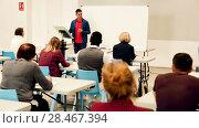 Купить «Smiling male teacher giving presentation for students in lecture hall», видеоролик № 28467394, снято 23 мая 2018 г. (c) Яков Филимонов / Фотобанк Лори