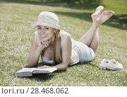Купить «Young barefoot woman lying on green grass», фото № 28468062, снято 22 июля 2019 г. (c) Яков Филимонов / Фотобанк Лори