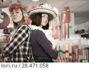 Купить «Girls posing back to back in festival accessories store», фото № 28471058, снято 15 марта 2018 г. (c) Яков Филимонов / Фотобанк Лори