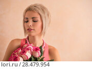 Young beautiful woman holding bouquet of pink roses. She is very satisfacted. Valentine's day or international women's day celebration. Стоковое фото, фотограф Kirill Kedrinskiy / Ingram Publishing / Фотобанк Лори