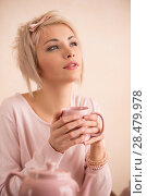 Young beautiful blond woman having tea-party. She is very satisfacted. Short hair and pink colors - modern style. Стоковое фото, фотограф Kirill Kedrinskiy / Ingram Publishing / Фотобанк Лори