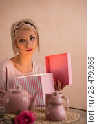 Young beautiful woman opening gift box while having tea-party. She is very satisfacted. Valentine's day or international women's day celebration. Стоковое фото, фотограф Kirill Kedrinskiy / Ingram Publishing / Фотобанк Лори