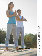 Купить «Fitness, sport, friendship and lifestyle concept - smiling couple making meditation yoga exercises on beach at morning», фото № 28480454, снято 22 июня 2014 г. (c) Ingram Publishing / Фотобанк Лори
