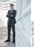 Portrait of handsome confident young businessman standing arms crossed, looking at camera. Full length portrait. Стоковое фото, фотограф Kirill Kedrinskiy / Ingram Publishing / Фотобанк Лори