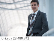 Portrait of handsome confident young businessman standing relaxed, smiling happy, looking at camera. Стоковое фото, фотограф Kirill Kedrinskiy / Ingram Publishing / Фотобанк Лори