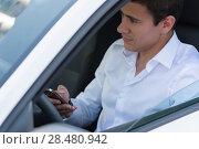 Купить «The young man behind the wheel driving car and calling phone», фото № 28480942, снято 20 июля 2014 г. (c) Ingram Publishing / Фотобанк Лори