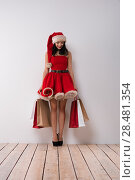 Купить «Christmas shopping. Pretty woman leaning on white wall with shopping bags, wearing red Santa Claus hat and dress», фото № 28481354, снято 15 октября 2014 г. (c) Ingram Publishing / Фотобанк Лори