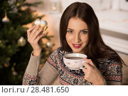 Купить «Beautiful woman wearing winter outfit drinking tea with candy at home near Christmas tree», фото № 28481650, снято 12 ноября 2014 г. (c) Ingram Publishing / Фотобанк Лори