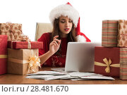 Купить «Young pretty woman wearing Santa Claus hat wrapping Christmas gift at her desk and responding to children messages and wishes by email», фото № 28481670, снято 12 ноября 2014 г. (c) Ingram Publishing / Фотобанк Лори