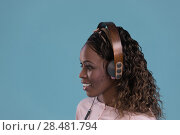 Купить «Happy African Woman listening to music on headphones. Young fresh African female model on blue background.», фото № 28481794, снято 19 ноября 2014 г. (c) Ingram Publishing / Фотобанк Лори